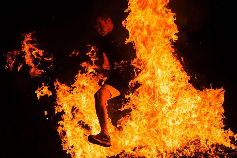 Muž skáče přes oheň během oslav noci svátého Juana ve Španělsku.