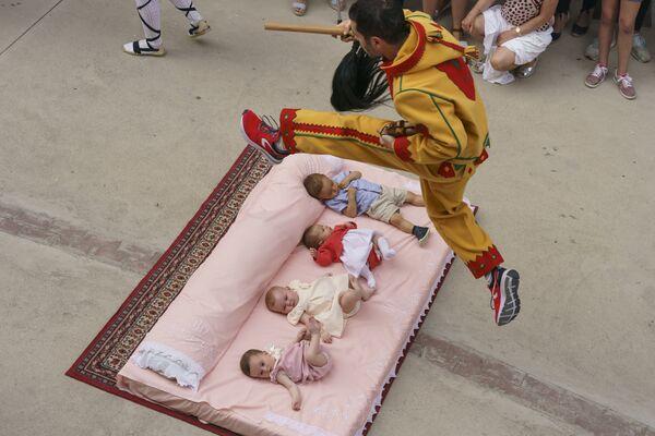 Muž v obleku ďábla skáče přes novorozence během každoročního festivalu El Colacho ve Španělsku. - Sputnik Česká republika