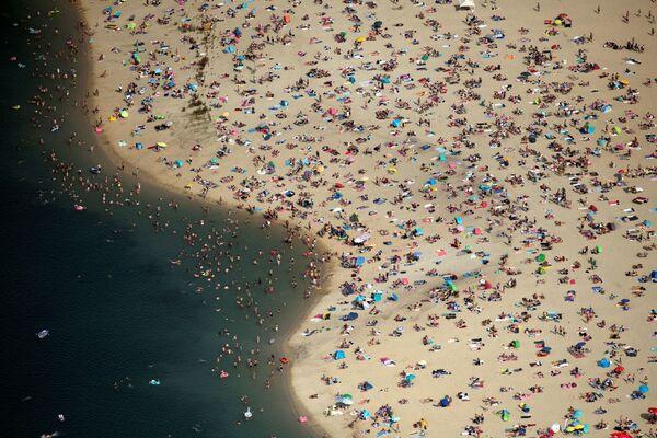 Lidé odpočívají na pláži za horkého počasí v Německu. - Sputnik Česká republika