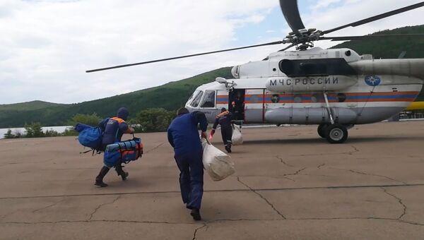 Záchranáři míří k vrtulníku pro oblet kolem zaplavených oblastí v Irkutské oblasti. - Sputnik Česká republika