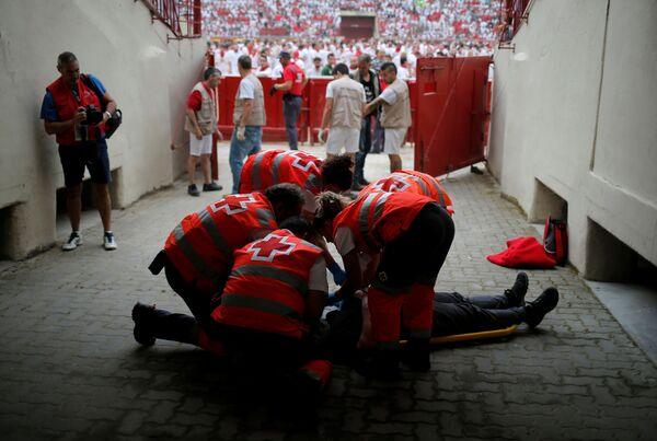 Lékaři pomáhají zraněnému během prvního běhu býků na festivalu San Fermín v Pamploně - Sputnik Česká republika