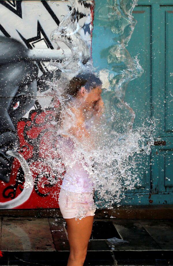 Dívku polévají vodou z balkonu během festivalu San Fermín v Pamploně, Španělsko - Sputnik Česká republika