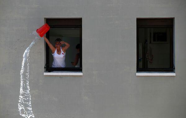Žena vylévá vodu na účastníky festivalu San Fermín v Pamploně, Španělsko - Sputnik Česká republika