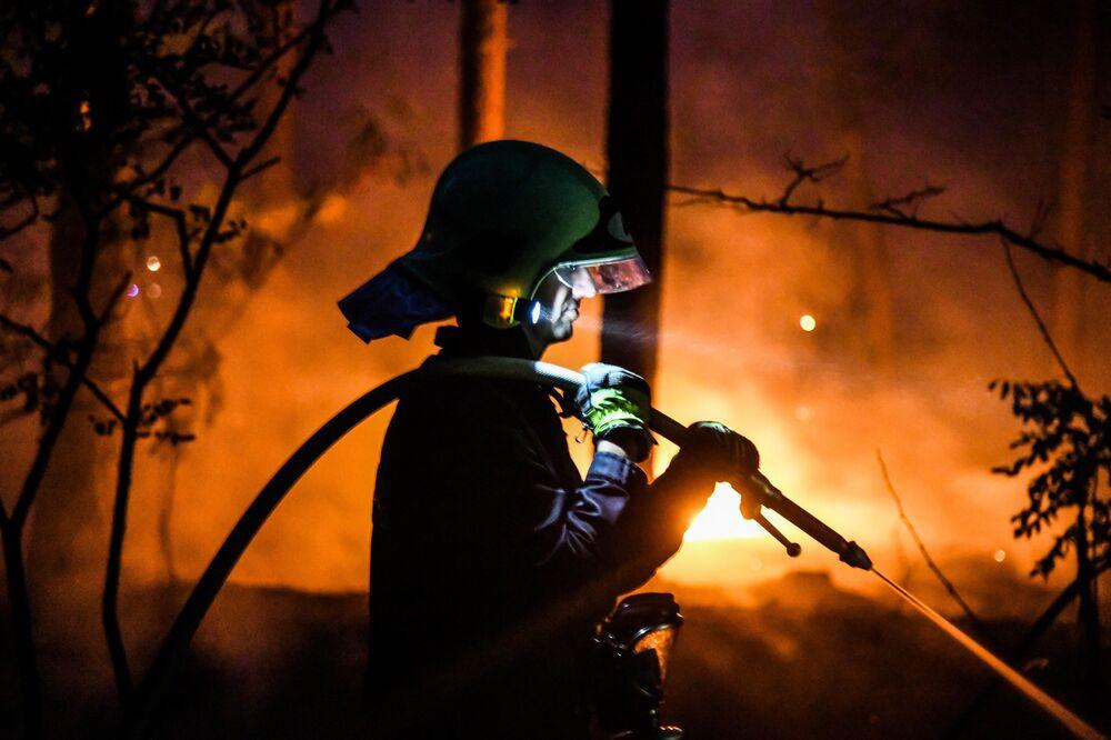 Hasič hasí lesní požár v Ciltendorfu vedle Frankfurtu nad Odrou, severovýchodní Německo, vedle hranice s Polskem.
