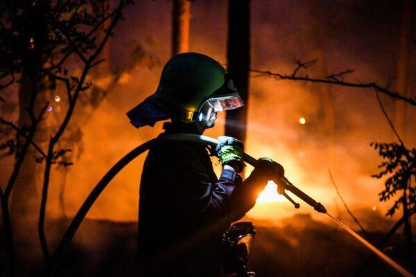 Hasič hasí lesní požár v Ciltendorfu vedle Frankfurtu nad Odrou, severovýchodní Německo, vedle hranice s Polskem. - Sputnik Česká republika