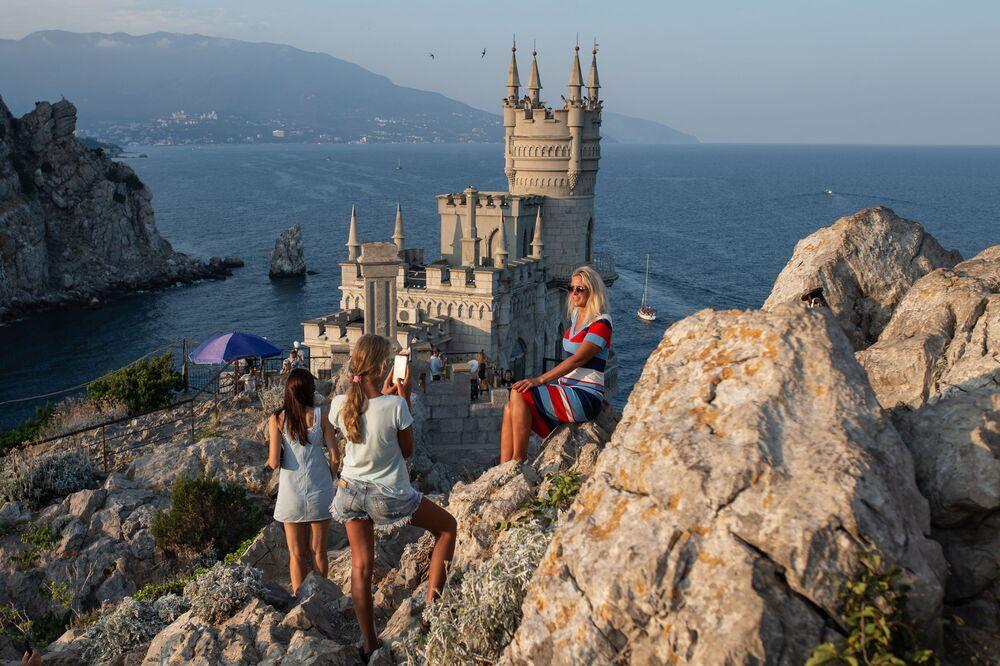 Turisté se fotí před hradem Vlaštovčí hnízdo s výhledem na Černé moře v obci Gaspra na Krymu.