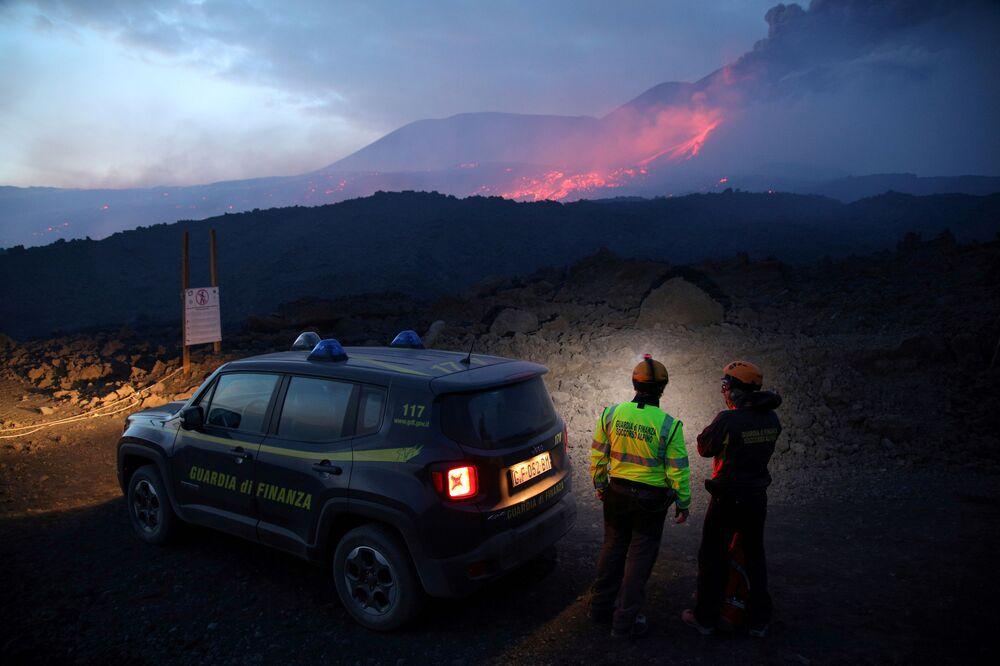 Zaměstnanci italské daňové policie sledují erupci sopky Etna na Sicílii.