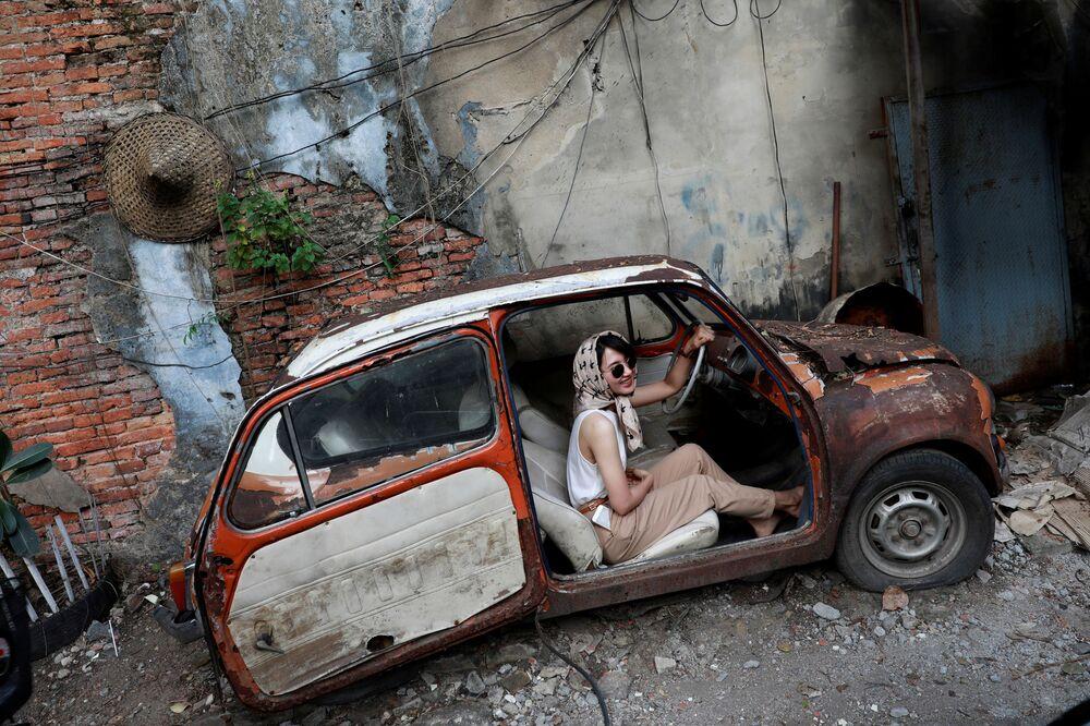 Dívka pózuje ve starém autě v turistické oblasti Bangkok v Thajsku.