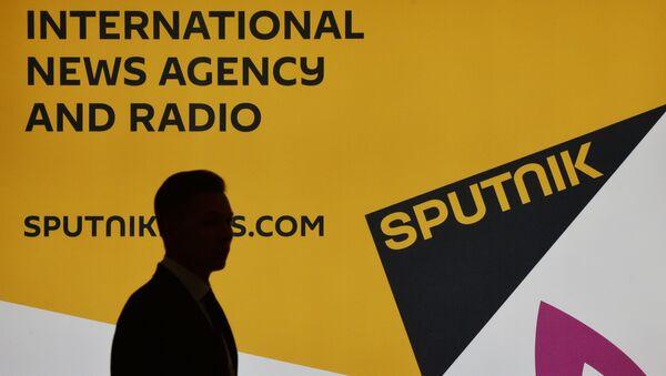 Účastník VEF vedle stánku mezinárodní tiskové agentury Sputnik. - Sputnik Česká republika