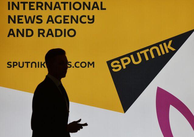 Účastník VEF vedle stánku mezinárodní tiskové agentury Sputnik.