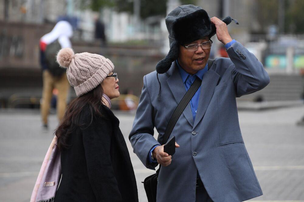 Turisté si oblékají čepice na Manéžním náměstí v Moskvě. V noci 5. srpna teplota v hlavním městě Ruska klesla na 6,7 °C.