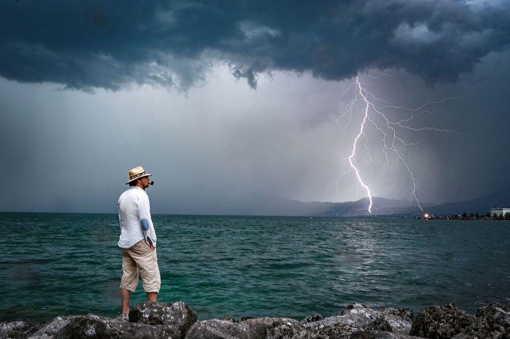 Muž na pozadí blesku. Ženevské jezero ve Švýcarsku.