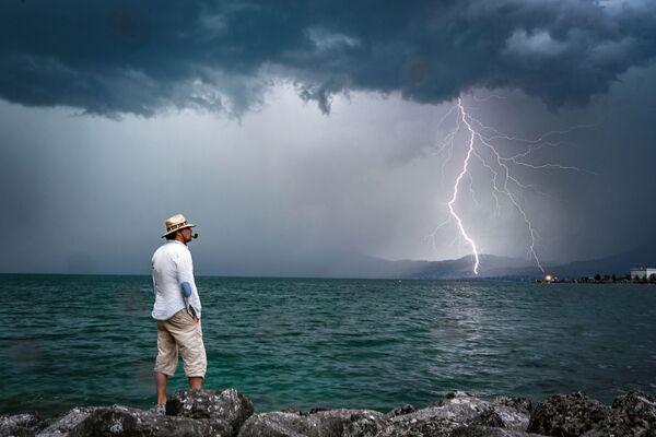 Muž na pozadí blesku. Ženevské jezero ve Švýcarsku. - Sputnik Česká republika