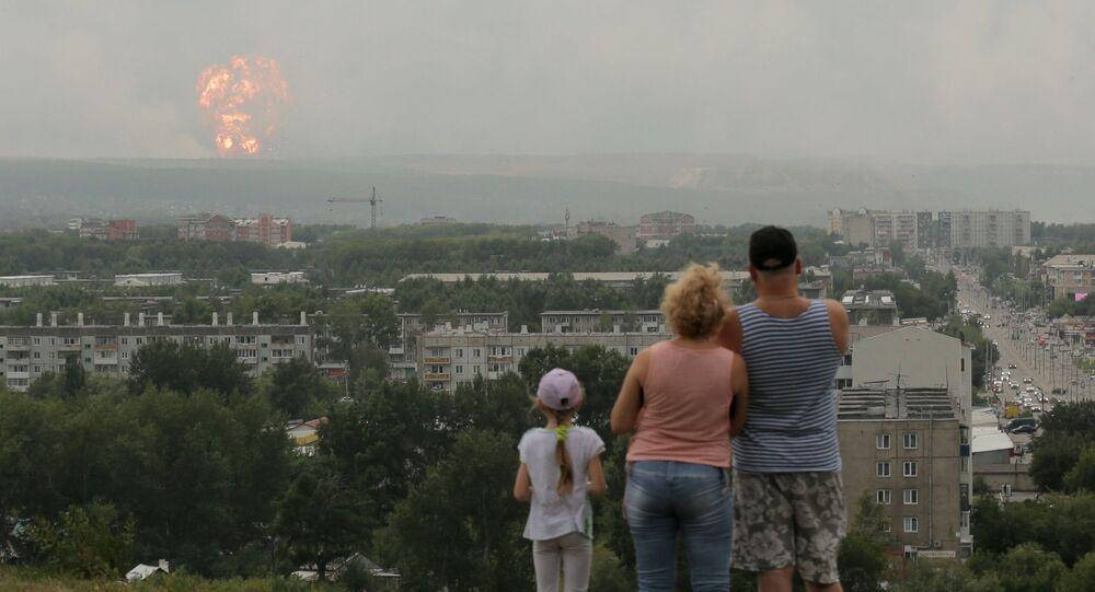 Občané pozorují kouř a oheň v místě výbuchu munice ve skladu nedaleko města Ačinsk v Krasnojarském kraji