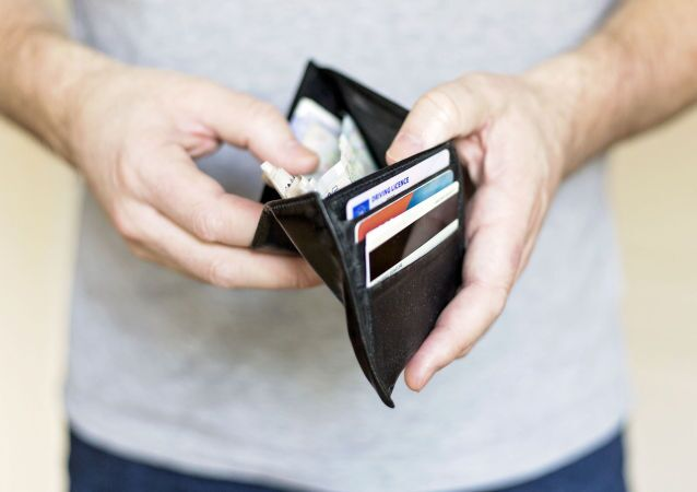 Muž drží peněženku s penězi