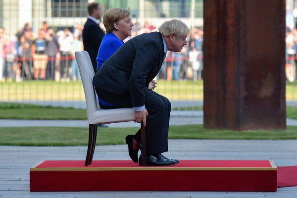 Německá kancléřka Angela Merkelová a britský premiér Boris Johnson během uvítacího ceremoniálu v rámci první zahraniční návštěvy Johnsona od nástupu do úřadu. - Sputnik Česká republika