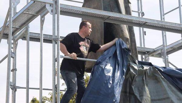 Aktivista strhává plachty ze sochy maršála Koněva - Sputnik Česká republika