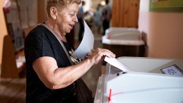 Žena hlasuje ve volbách v Simferopolu na Krymu - Sputnik Česká republika