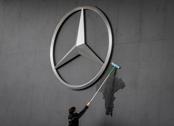 Pracovník čistí logotyp Mercedes na Frankfurtském autosalonu - Sputnik Česká republika