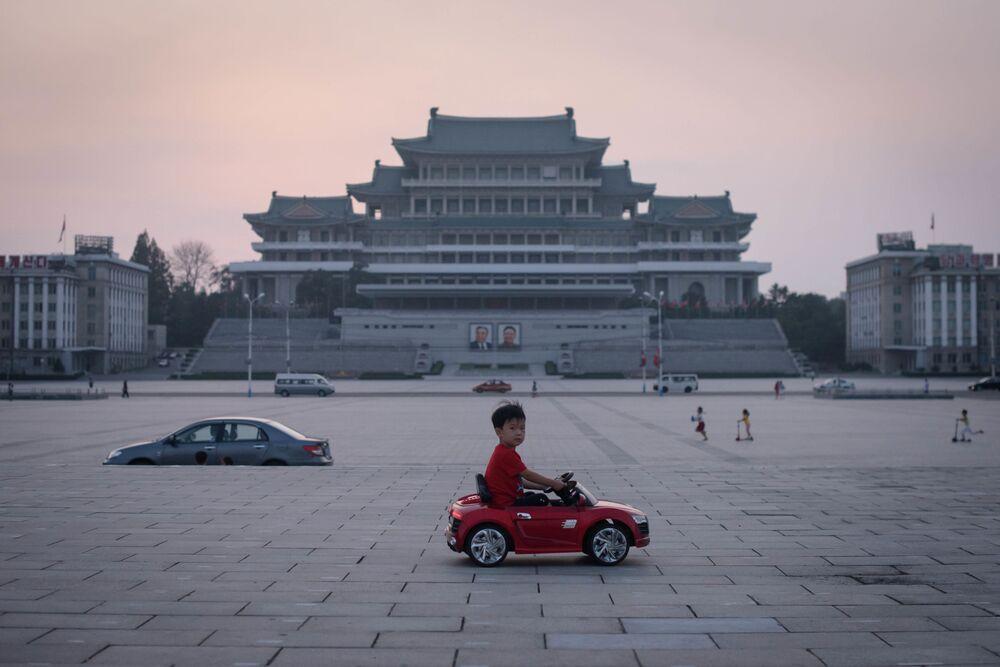 Chlapec na autíčku na náměstí Kim Ir-sena v Pchjongjangu, Severní Korea.