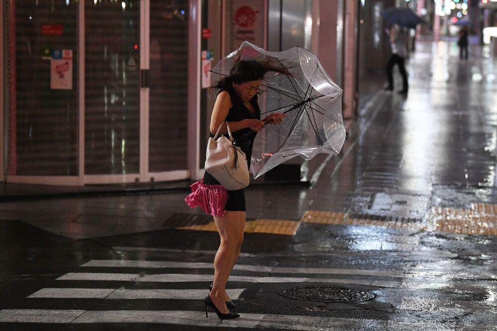 Žena s deštníkem v Tokiu, která se snaží schovat před silným deštěm a větrem.