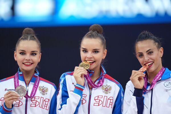 Vítězky vystoupení s míčem na Mistrovství světa v moderní gymnastice v Baku na slavnostním předávání cen (zleva doprava): Arina Averinová (Rusko) - stříbrná medaile, Dina Averinová (Rusko) - zlatá medaile, Lina Ashram (Izrael) - bronzová medaile. - Sputnik Česká republika