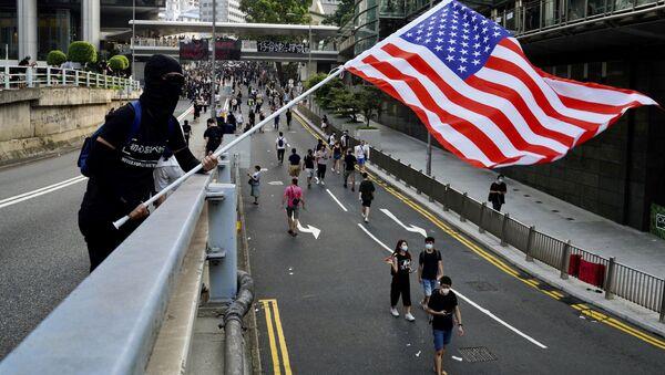 Demonstrant v Hongkongu mává americkou vlajkou - Sputnik Česká republika