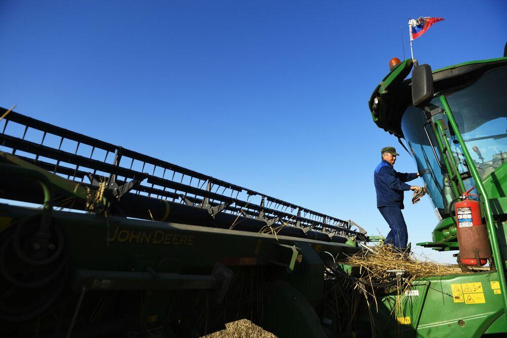Kombajnista kontroluje techniku během sklizení pšenice v Novosibirské oblasti.