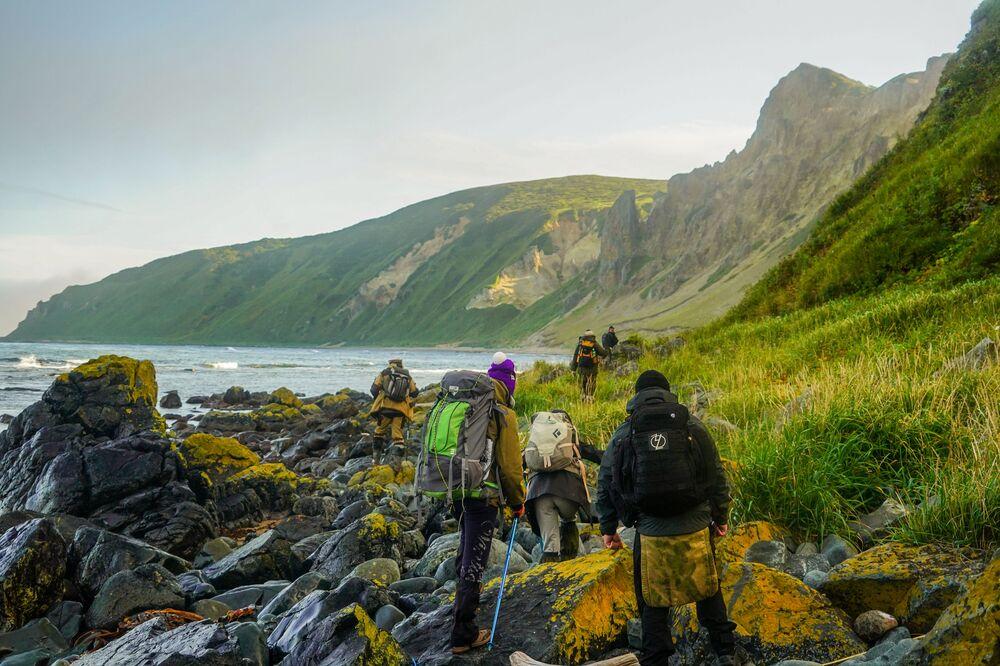 Členové expedice procházejí podél pobřeží Tetyaevského zálivu na ostrově Urup