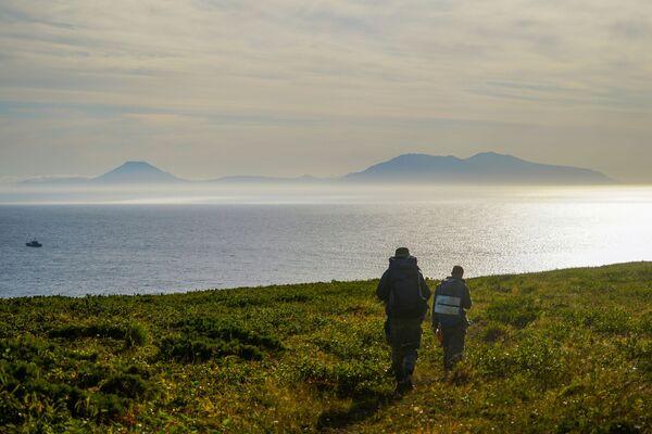 Členové expedice se dívají na úžinu Frieza a Iturup Island z pobřeží ostrova Urup  - Sputnik Česká republika
