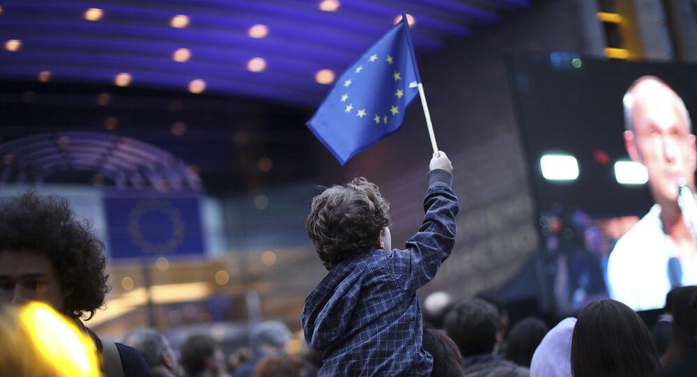 Malý chlapec s vlajkou Evropské unie u budovy Evropského parlamentu v Bruselu