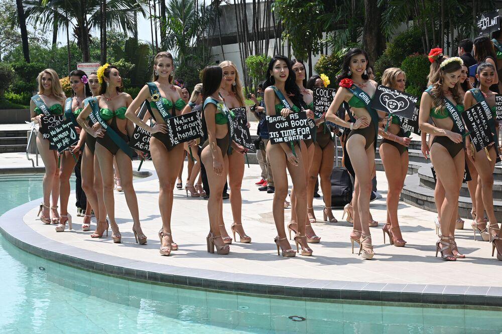 Modelky a uchazečky o titul Miss Earth 2019 držící transparenty s ekologickými slogany během prezentace v hotelu. Dne 2. října 2019, v Manile.