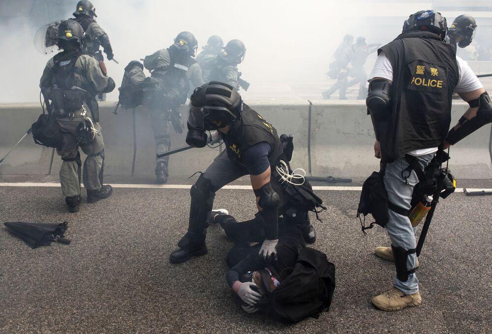 Policisté zadržují demonstranty v Hongkongu.