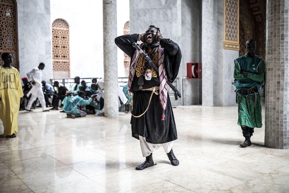 Stoupenec Baye Fall zpívá na výstupu z mešity.