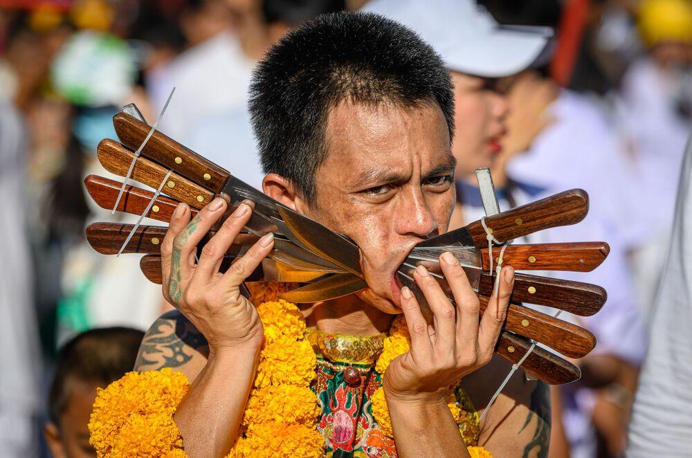 Účastník festivalu vegetariánství s propíchnutými noži ve tvářích v Thajsku.