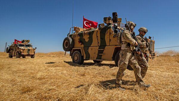 Američtí vojáci prochází okolo tureckého obrněného vozidla v okolí města Tell Abiad - Sputnik Česká republika