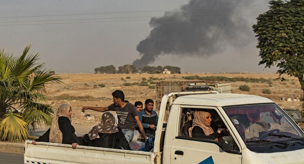 Lidé utíkají před tureckým náletem na město Ras al-Ain v syrské provincii Hasaka (9. 10. 2019)