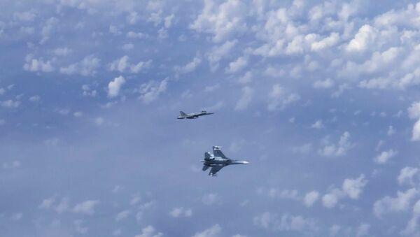Letoun Su-27 vytlačuje stíhačku NATO F-18, která se přiblížila k letadlu ruského ministra obrany Sergeje Šojgu nad neutrálními vodami Baltského moře - Sputnik Česká republika
