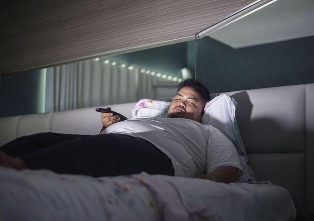 Muž spí před televizí