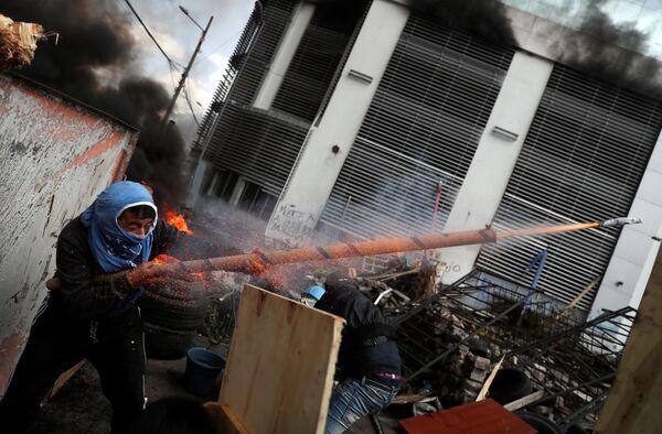 Demonstrant střílí ze zbraně vlastní výroby během protestů v ekvádorském Quito. - Sputnik Česká republika
