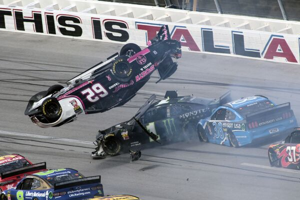 Auto pilota Brendana Gaughana letí nad auty Kurta Busche a Davida Ragana během zápasu NASCAR Cup Series v USA. - Sputnik Česká republika