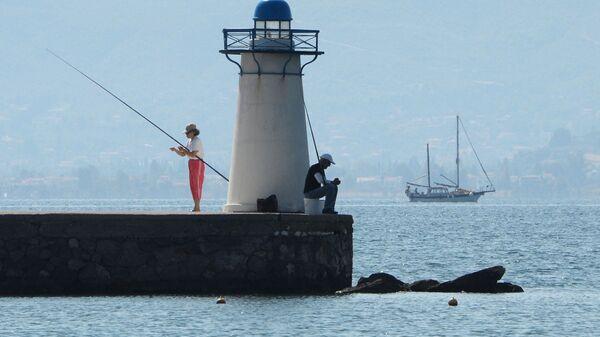 Отдыхающие ловят рыбу возле маяка в заливе Нотиос-Эввоикос Эгейского моря - Sputnik Česká republika