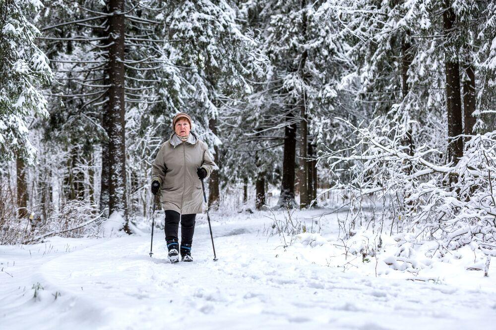 Žena se zabývá severskou chůzi v městském parku Veverčí ostrov v Petrozavodsku.