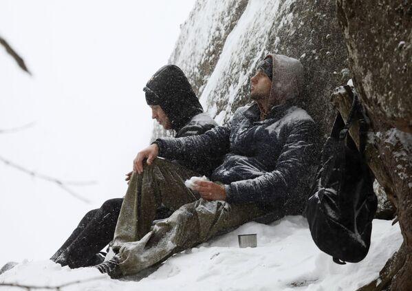 Turisté odpočívají pod syenitovou skálou Lví brána. - Sputnik Česká republika