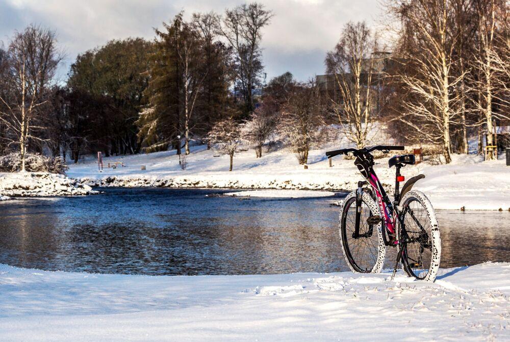 Kolo na zasněžené cyklistické stezce na břehu řeky Lososinki v centru Petrozavodsku.
