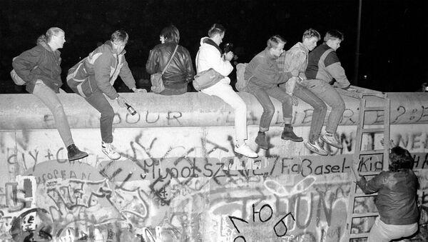 Horní snímek zachycuje občany západního Německa, kteří sedí na Berlínské zdi na ulici Zimmer Strasse 9 (dne 9. listopadu 1989). Dolní snímek zachycuje stejné místo ze dne 30. října 2019. - Sputnik Česká republika