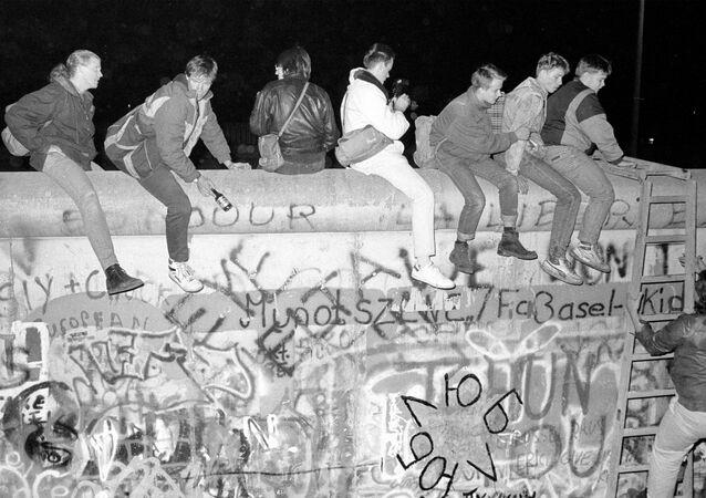 Horní snímek zachycuje občany západního Německa, kteří sedí na Berlínské zdi na ulici Zimmer Strasse 9 (dne 9. listopadu 1989). Dolní snímek zachycuje stejné místo ze dne 30. října 2019.