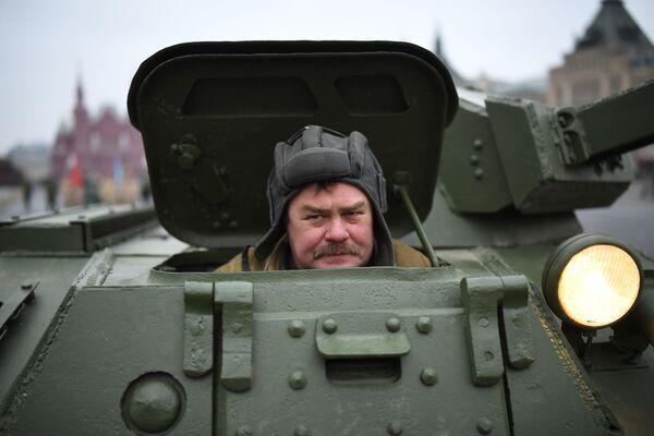 Muž v sovětské uniformě vykukuje z tanku během generální zkoušky pochodu věnovanému 78. výročí vojenské přehlídky z roku 1941 na Rudém náměstí  - Sputnik Česká republika