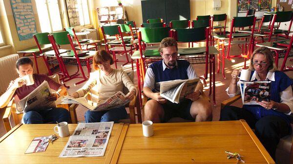 Учителя с газетами в пустом классе гимназии в Праге - Sputnik Česká republika