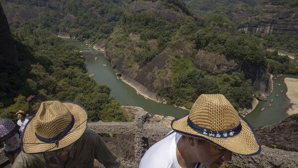 Návštěvníci lezou na vrchol Tianyu v pohoří Wu-i v provincii Fu-ťien ve východní Číně  - Sputnik Česká republika